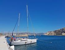 Ratonneau wyspa, Francja/- mogą 8, 2017: Załoga sailingboat przygotowywa nasz jacht żeglować Mały jachtu cumowanie blisko mola w  Fotografia Royalty Free