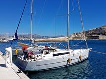 Ratonneau wyspa, Francja/- mogą 8, 2017: Załoga sailingboat przygotowywa nasz jacht żeglować Mały jachtu cumowanie blisko mola w  Obrazy Stock