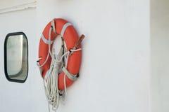 Ratownik, Pomarańczowy życie pierścionek wspinał się na łódkowatym pobliskim porthole Zdjęcie Stock