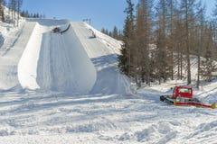 Ratrak som gör det halva röret att slutta för snowboard och att skida Royaltyfri Foto