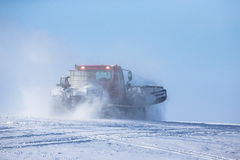 Ratrak in a spray of snow against the blue sky Royalty Free Stock Photography
