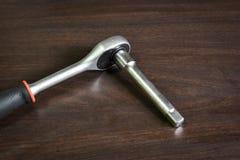 Ratschenschlüssel mit dem ausgedehnten Adapter, der auf Holztisch liegt Stockfotos
