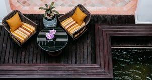 Rattan łozinowych krzeseł colourful poduszki i poduszki na drewnianych półdupkach zdjęcia royalty free