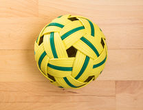 Rattan ball lying on beech floor Stock Image