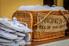 Rattan basket with white flip-flops of different sizes for guests, with a writing DANCING SHOES. KICK OFF YOUR HEELS!. Basket with white flip-flops of different Stock Photography