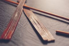 Rattan cane and leather tawse for punishment. Traditional corporal punishment implements on dark background Stock Image