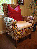 Rattan Chair. With a red pillow white cushion on carpet Stock Photography