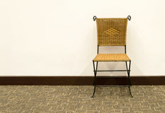 Rattan chair against a white wall Royalty Free Stock Photography