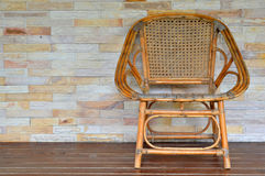 Rattan chair. Handmade rattan chair and brick wall background Stock Image