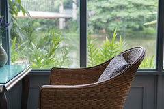 Rattan chair with pillow in living room in modern house beside w Royalty Free Stock Photography