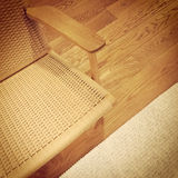 Rattan chair and rug on wooden floor Royalty Free Stock Photos