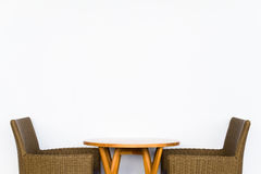 Rattan Chairs on Blank White Wall. Rattan chairs and wood table on blank white wall for text or picture Stock Image