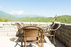 Rattan chairs and table on terrace in mountains. Stock Photo