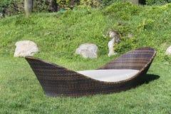 Rattan da sala de estar sunbed em um jardim verde Imagem de Stock