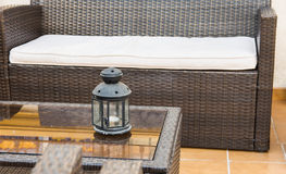 Rattan furniture, sofa armchairs, glass coffee table with candle holder, fragment of patio, porch, mediterranean Royalty Free Stock Photography