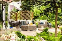 Rattan garden furniture and hanging chair on wooden terrace of h. Ouse. Real photo stock photo