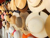 Rattan-Hüte, die an der Wand-Hintergrund-Beschaffenheit hängen stockfoto