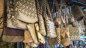 Rattan handbag with Dayak tribal pattern. Rattan handbag with Dayak indigenous people of Borneo tribal pattern hanging in front of souvenir shop in Samarinda Royalty Free Stock Photography