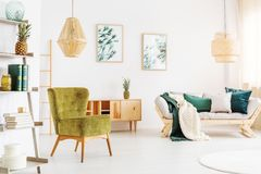 Rattan lamps in living room. Two rattan lamps in bright living room with moss green chair and pineapple on shelf royalty free stock photography