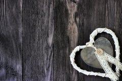 Rattan and metal heart on dark wood Royalty Free Stock Photo