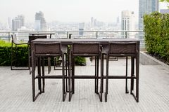 Rattan one table with two stool chairs standing against the ter Royalty Free Stock Image