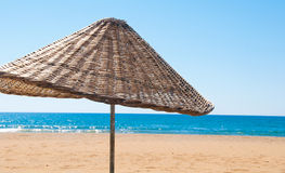 Rattan parasol of wicker at the seaside Stock Photos