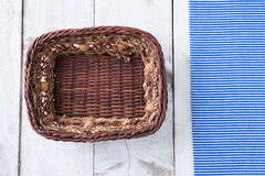 Rattan plate or basket on wooden table and tablecloth on table w Stock Photography