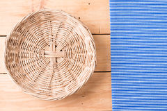 Rattan plate or basket on wooden table and tablecloth on table w Stock Photo