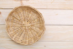 Rattan plate or basket on wooden table Royalty Free Stock Photos