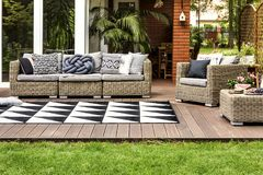 Rattan sofa on terrace. Rattan sofa and armchair with pillows on a wooden terrace of a modern house stock image