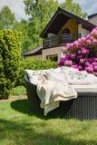 Rattan sofa with decorative cushions. Photo of rattan sofa with decorative cushions beside blooming bush Stock Photos
