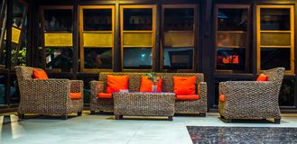 Rattan sofa with orange cushion in the lobby of a hotel. With many windows at night. interior design concept stock photo