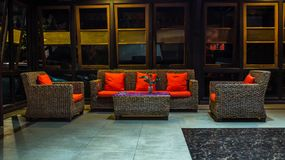 Rattan sofa with orange cushion in the lobby of a hotel. At night. interior design concept stock photo