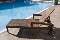Rattan sun lounger with wheels. Luxury brown wicker rattan lounger sunbed by the blue swimming pool royalty free stock image