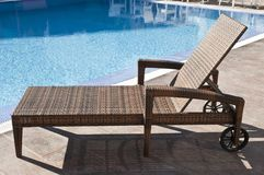 Rattan sun lounger with wheels. Luxury brown wicker rattan lounger sunbed by the blue swimming pool, side view stock photos