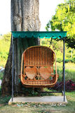 Rattan swing bench in garden. With couple of heart shape decoration Stock Images