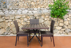 Rattan table and chairs in cafe against stone wall Royalty Free Stock Photos