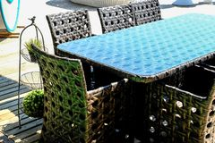 Rattan table and chaise longues near modern swimming pool, closeup royalty free stock photos