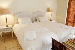 Rattanbett mit weißen Bedsheets und Osmanen Stockfotografie