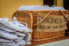 Rattankorb mit weißen Flipflops von verschiedenen Größen für Gäste, mit ein Schreiben TANZEN-SCHUHEN TRETEN SIE WEG IHRE FERSEN! Stockfotografie