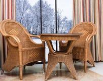 Rattanmöbel nahe dem Fenster mit einer Winterlandschaft Stockbilder