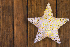 Rattans shining white Christmas star on weathered plank wood background, copy space for text, template for greeting card Royalty Free Stock Photo