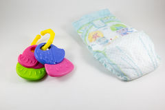 Rattle and diaper on a white background Royalty Free Stock Image