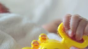 Rattle Toy In the baby Hand. Baby Playing With A Yellow Plastic Crab Toy In the Hand stock video
