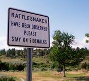 Rattlesnake warning sign. A rattlesnake warning sign asking you to stay on sidewalk Stock Photography