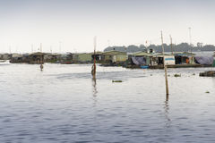 Ratty boats and raft houses with fish cages floating on Mekong river Stock Photos