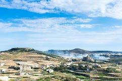 Rauch steigt in die Rollenlandschaft von Gozo, Malta Stockfotos