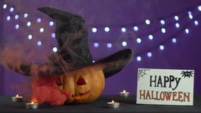 Rauch und Funken gehen vom Kürbis Stapelschachtkürbis mit Hut in der Dunkelheit stock video