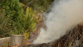 Rauch von gebranntem Stroh im Garten mit Weinlese-Stahl-Eimer lizenzfreie stockfotos