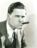 Rauchen einer Zigarre mit Haltung Stockbild